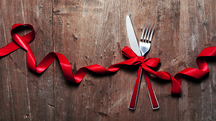 Knife and fork with a red holiday ribbon