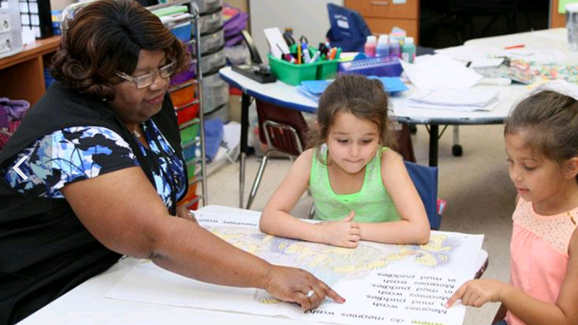 Foster grandparent Gladys Everett tutors students at Oak Grove Elementary. (Photo from the Tampa Bay Business Journal and Seniors in Service of Tampa Bay.)