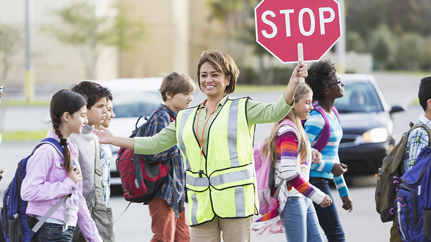 Female crossing guard holding a stop sign helping kids to cross the street