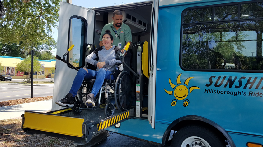 Dispatch Supervisor Gustavo Toro helps student Jalize Ginarte try out the wheelchair lift on a Sunshine Line bus