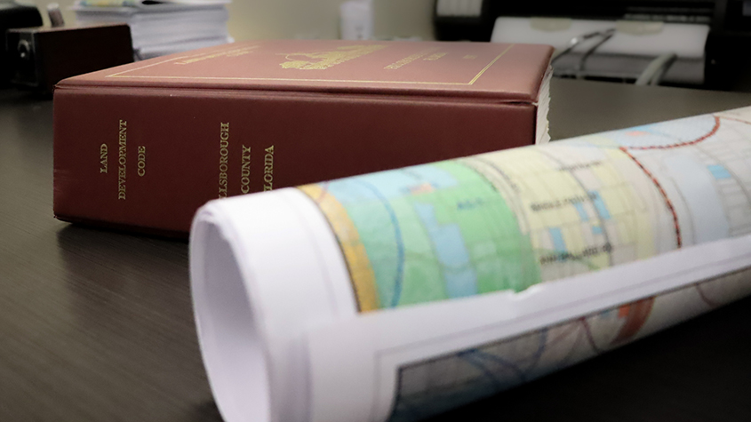 Hillsboorugh County Land Development Code book sitting on a desk with a rolled up map in front of it