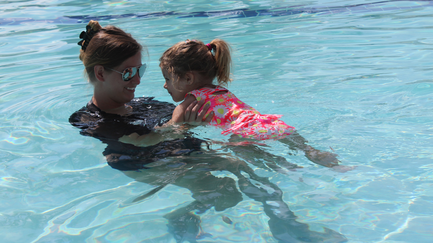 Instructor swimming with child